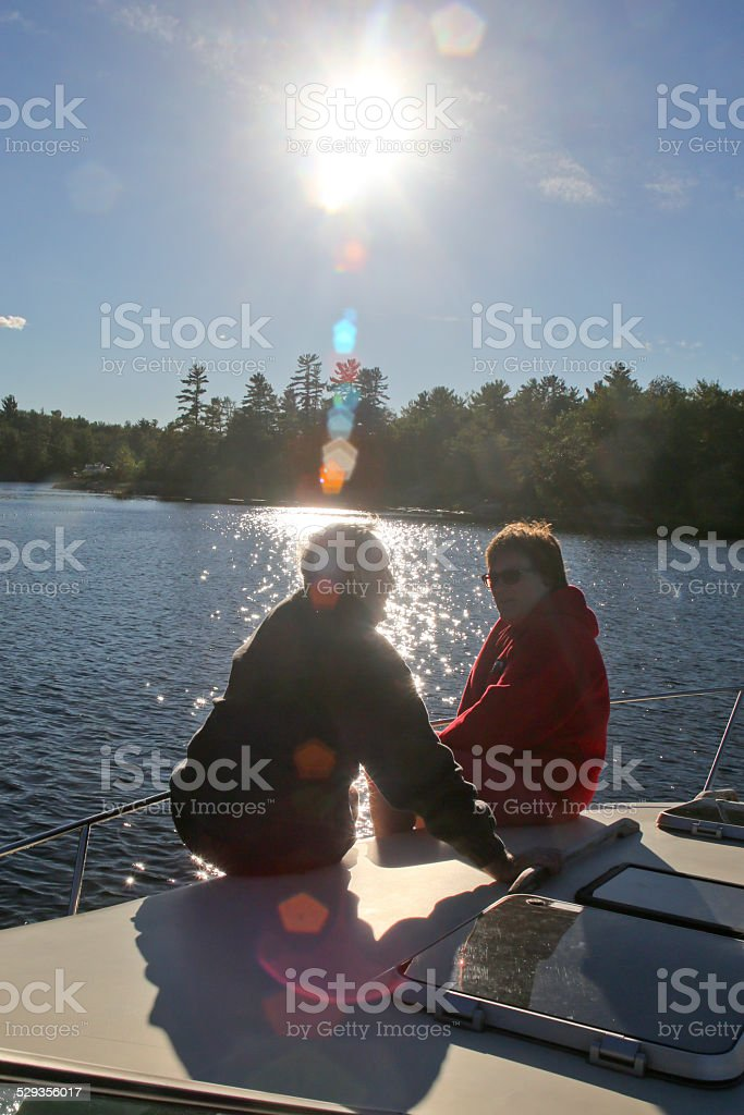 Two Mature Adults on Yacht Foredeck on Georgian Bay stock photo