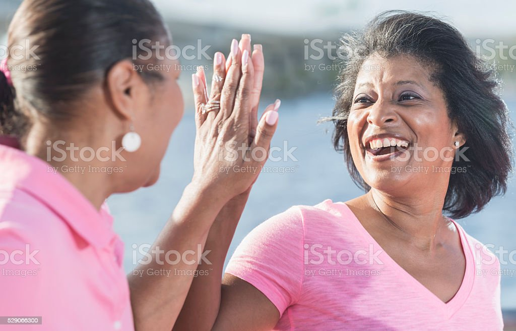 Two mature African American woman in pink, high fives stock photo