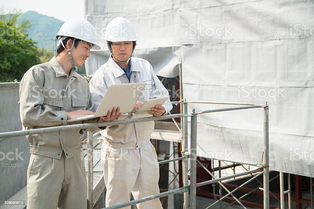 Two mature construction workers talking and looking at plans stock photo