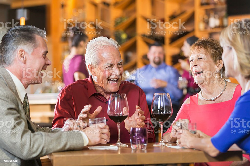Two mature couples having drinks at restaurant stock photo