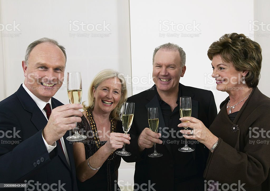 Two mature couples raising glasses of white wine, smiling royalty-free stock photo