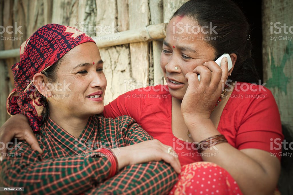 Two mature, Nepalese women talking on phone happily. stock photo
