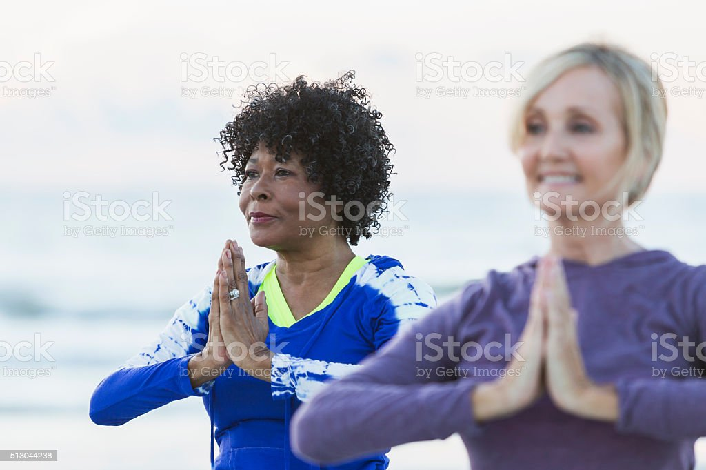 Two mature women exercising on beach, doing yoga stock photo