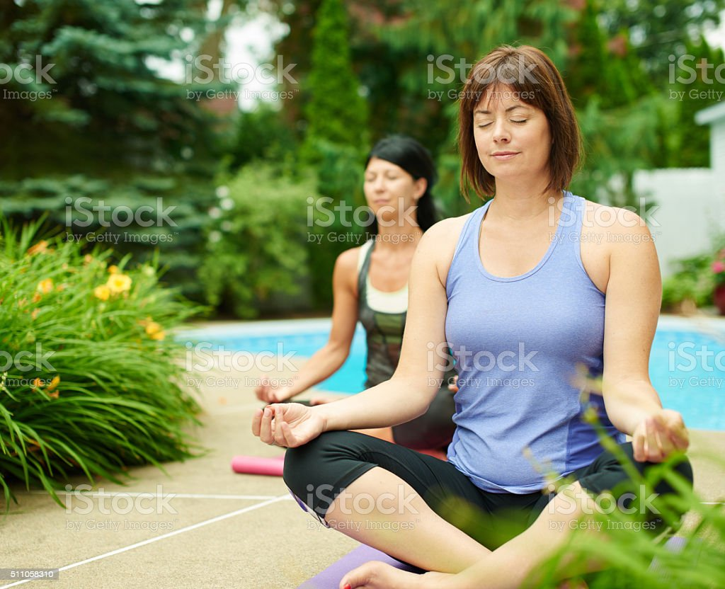 Two mature women keeping fit by doing yoga in the stock photo