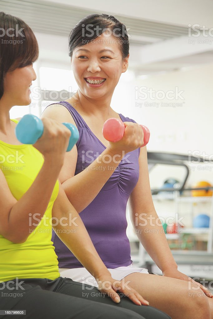 Two mature women lifting weights in the gym royalty-free stock photo