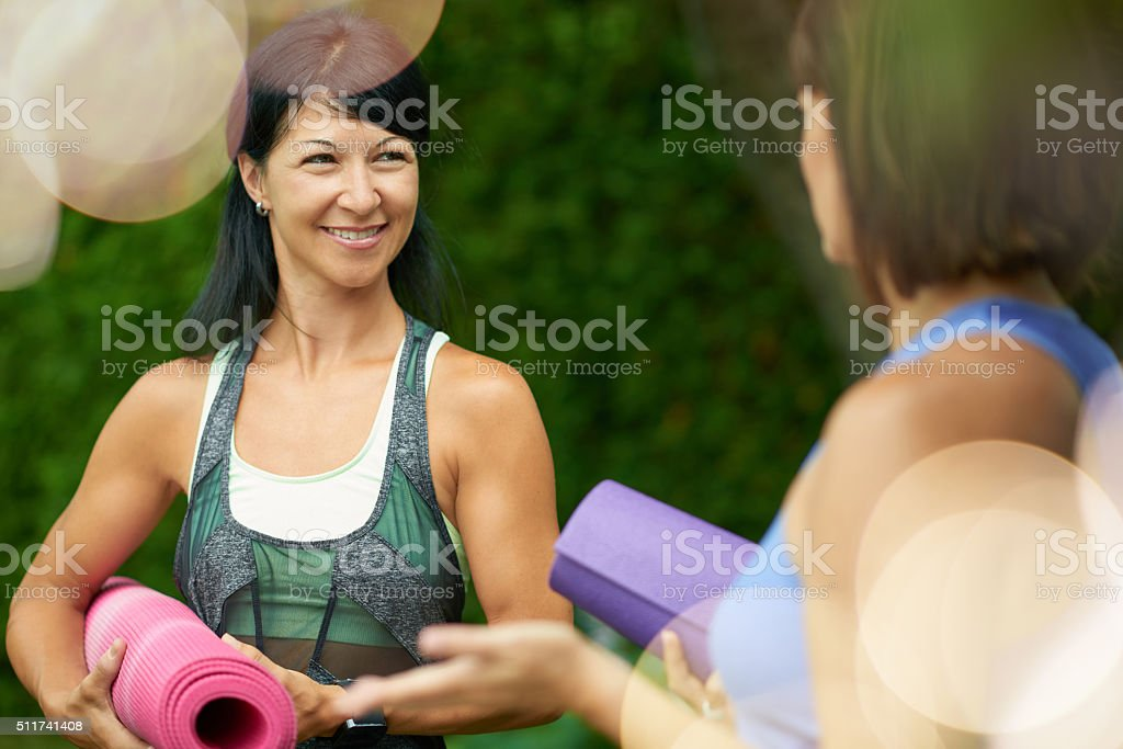 Two mature women talking before doing yoga in the summer stock photo