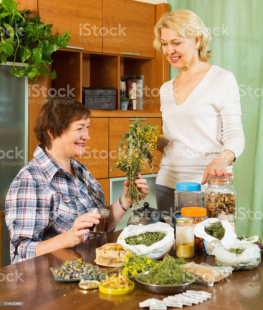 Two mature women with  herbs stock photo