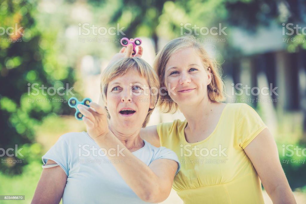 Two mature women with spinner in hands stock photo