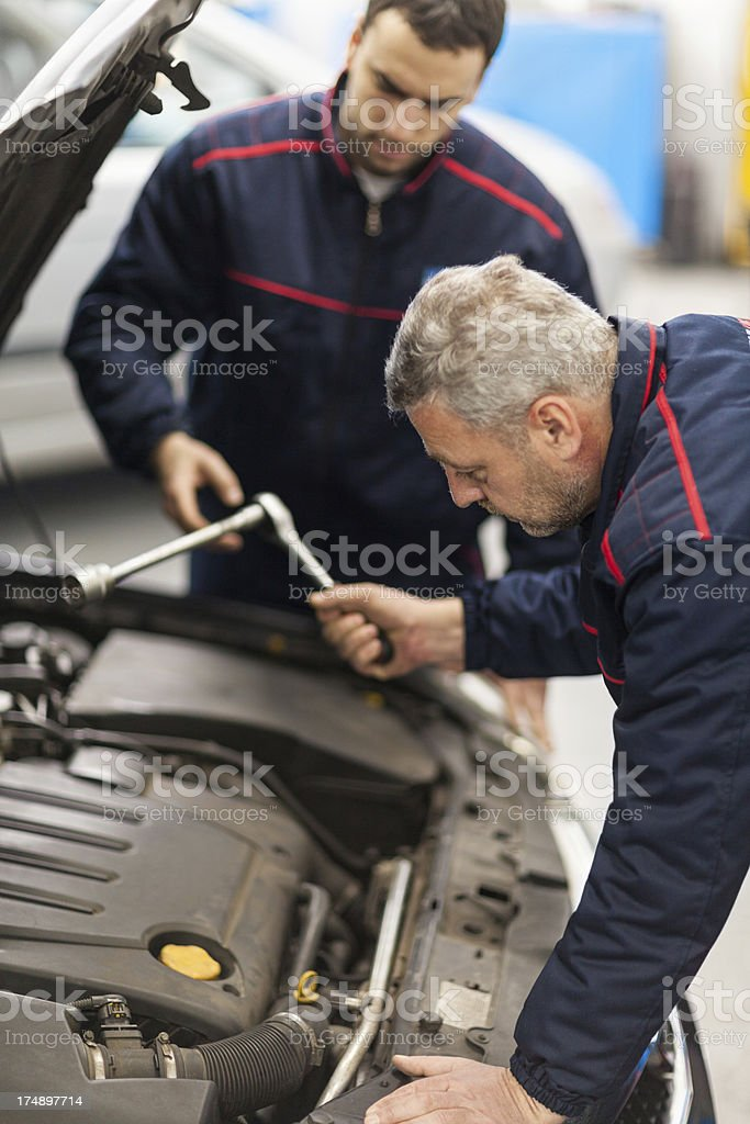 Two mechanic colleagues servicing car at repair shop royalty-free stock photo