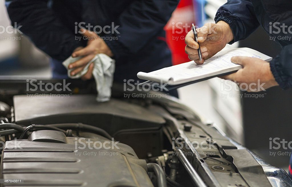Two mechanic colleagues servicing car at repair shop stock photo