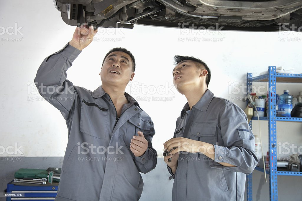 Two Mechanics Looking at Underside of a Car royalty-free stock photo