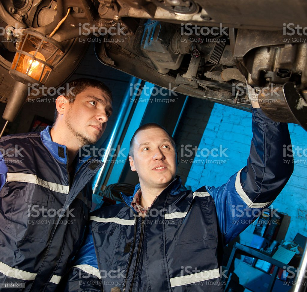 Two mechanics working under car in workshop royalty-free stock photo