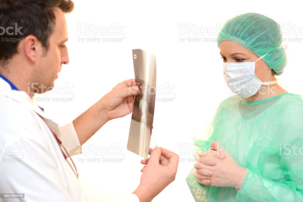 Two medical doctors examining X-ray scan and preparing for surgery stock photo