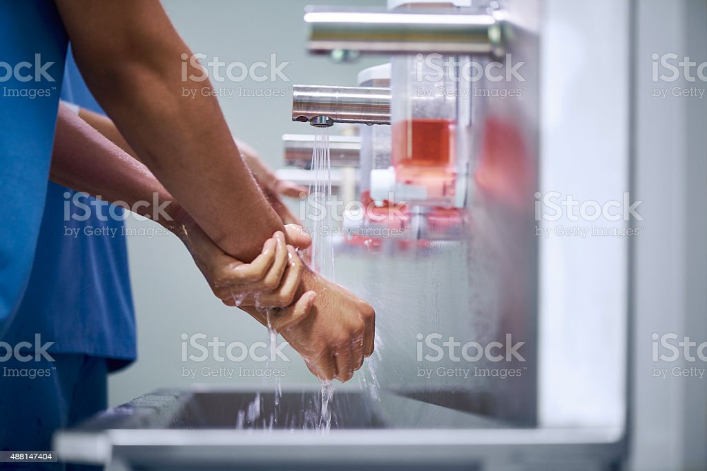 two medical professionals scrubbing up stock photo