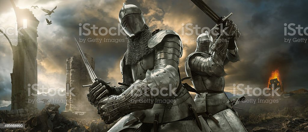 Two Medieval Knights With Swords On Battlefield Near Ruined Monuments stock photo