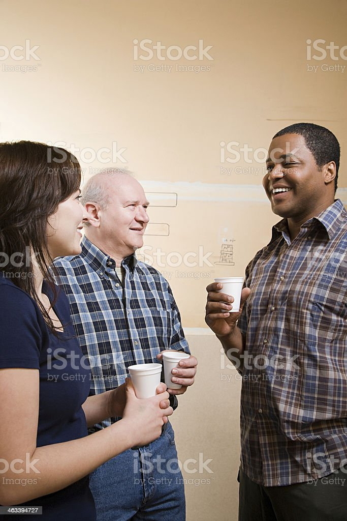 Two men and a woman drinking coffee and talking stock photo