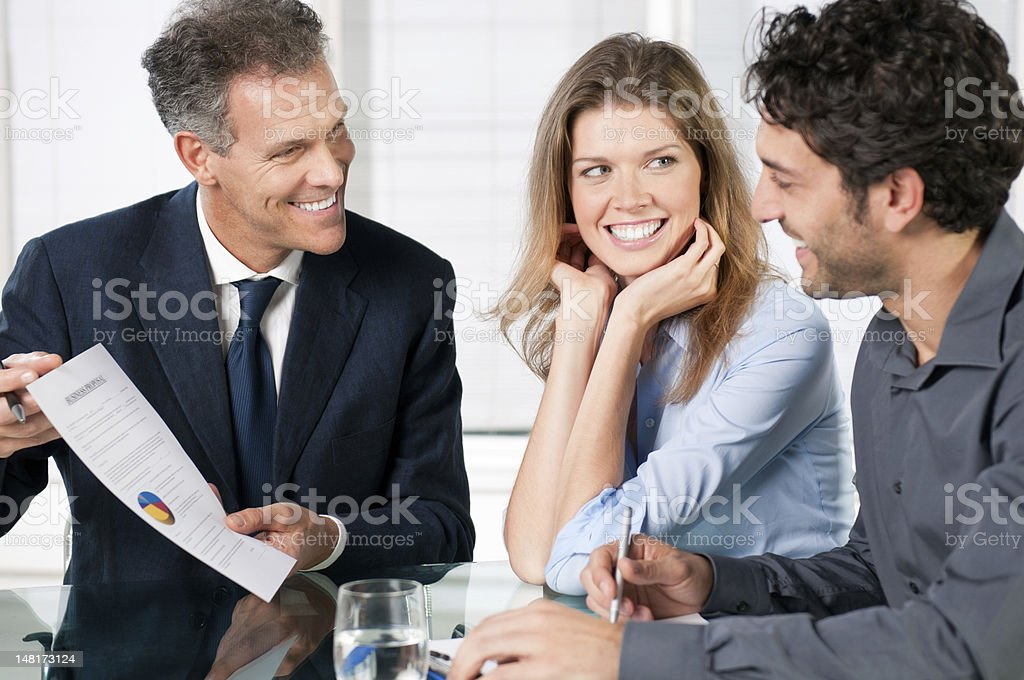 Two men and a woman looking over a business proposal stock photo