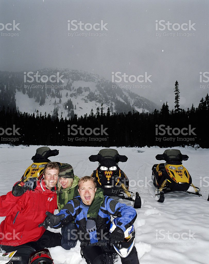 Two men and woman sitting on snow by snowmobiles, portrait royalty-free stock photo