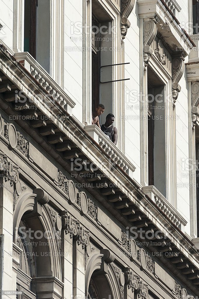 two men are looking out of house in havana, cuba royalty-free stock photo