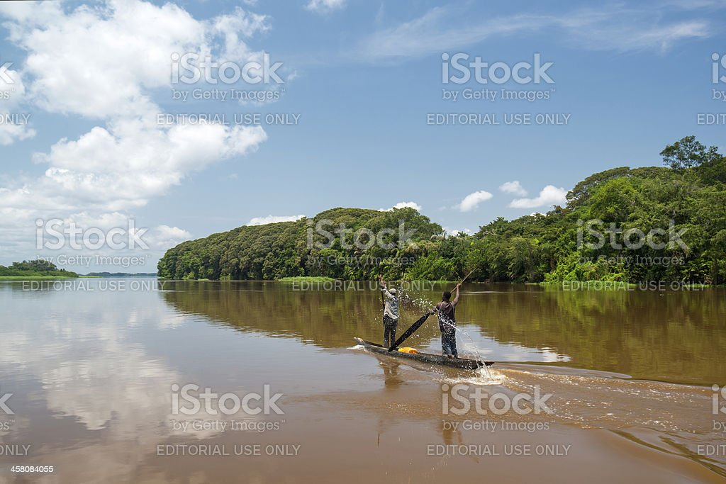 Two men are paddling in a pirogue on Congo River royalty-free stock photo
