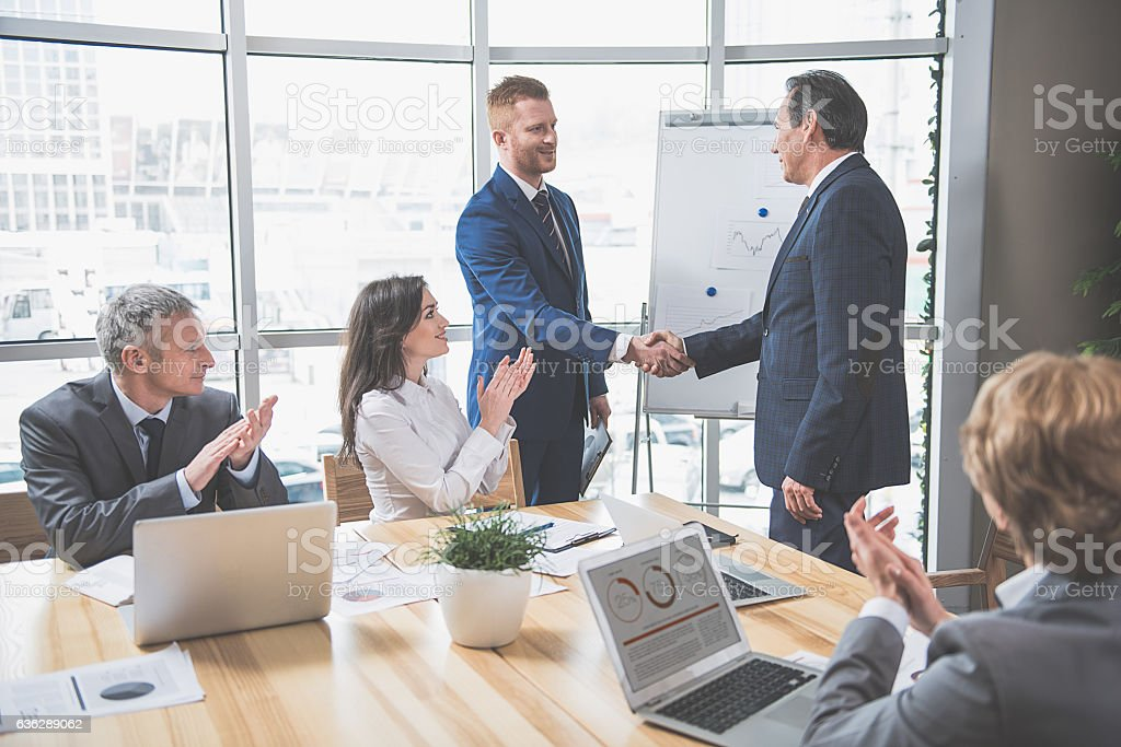 Two men are shaking hands stock photo