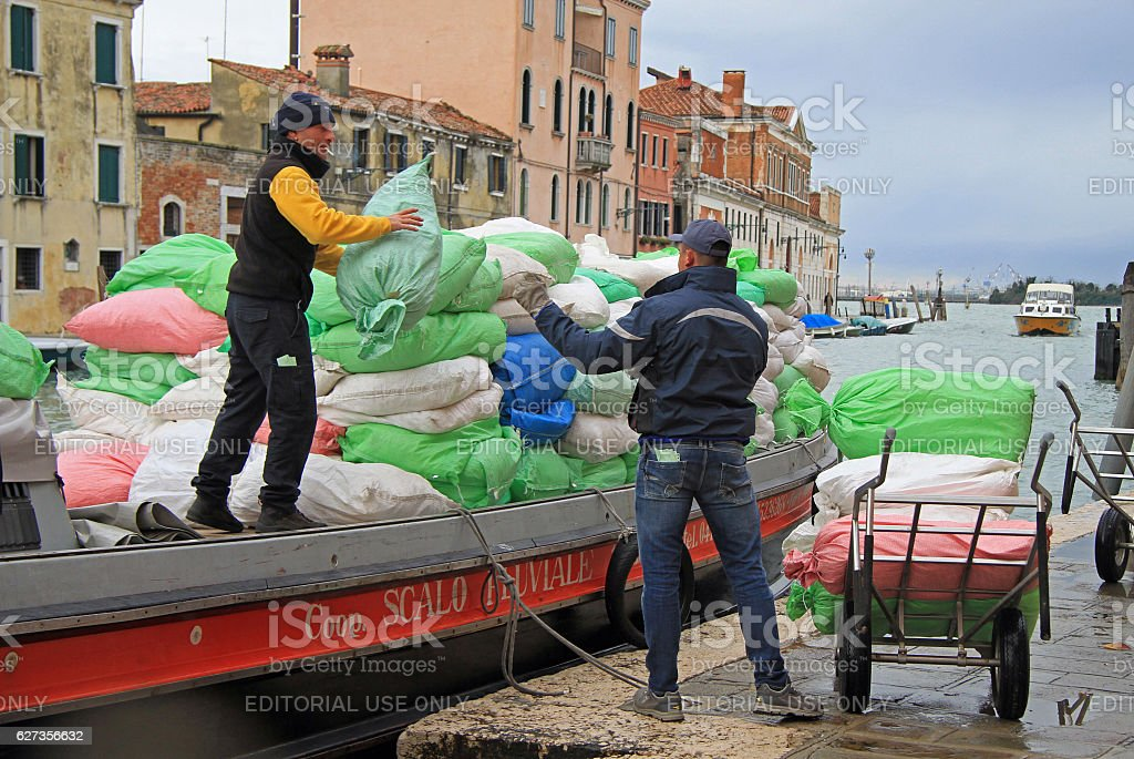 two men are unloading sacks from the boat in Venice stock photo