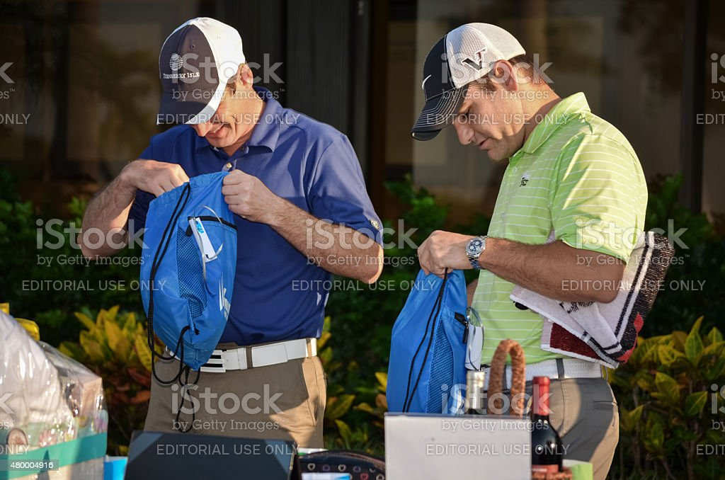 Two men at a golf charity event with goody bags stock photo