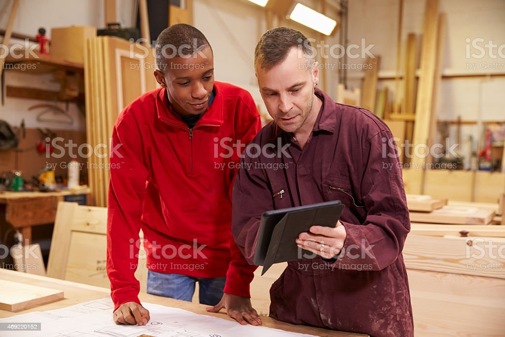 Two men at a wood shop looking at a tablet stock photo