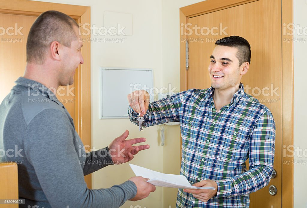 Two men at doorway with keys and contract stock photo