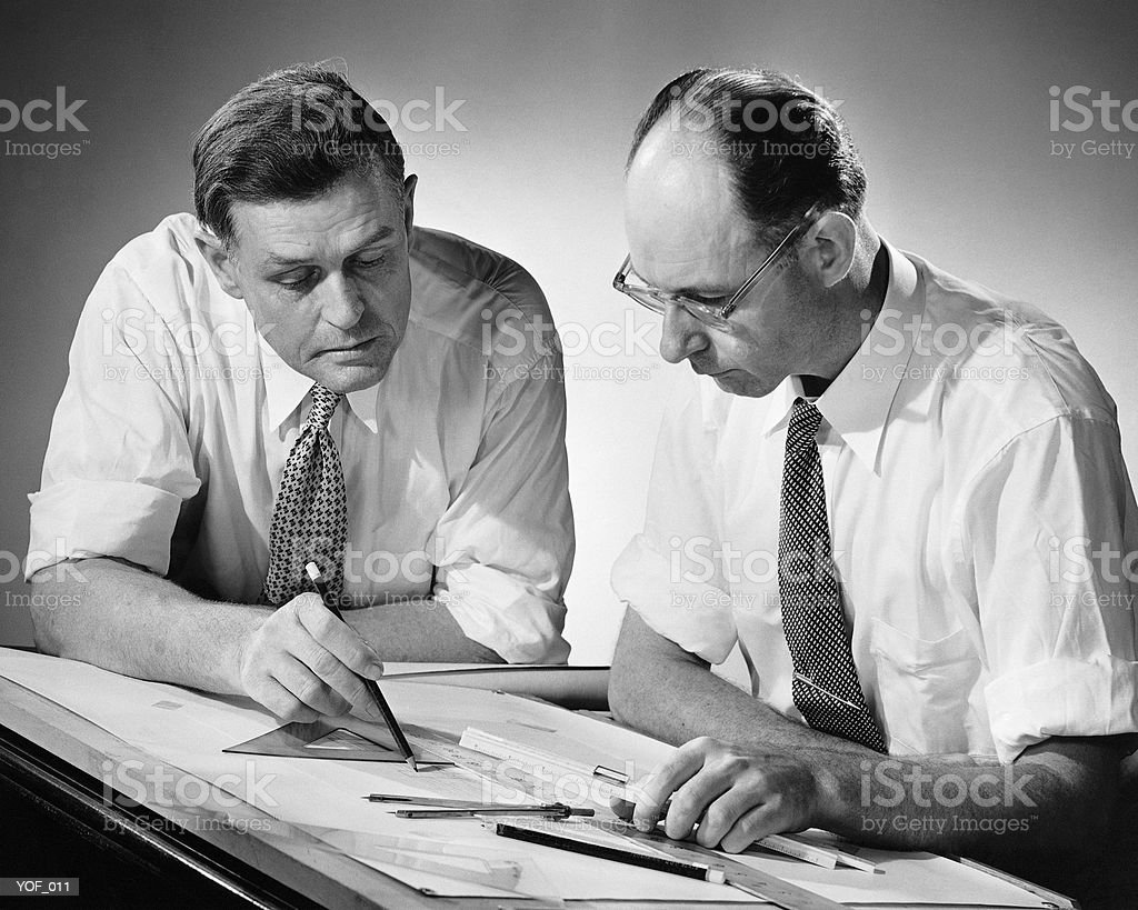 Two men at drafting table stock photo
