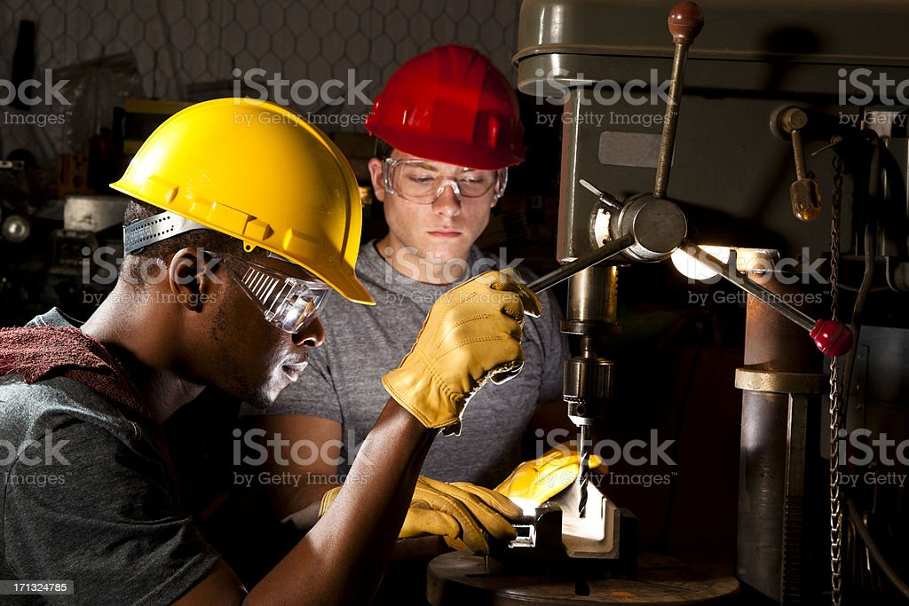 Two men at drill press in workshop stock photo