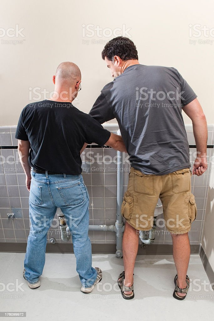 Two Men at the Bathroom Urinals stock photo