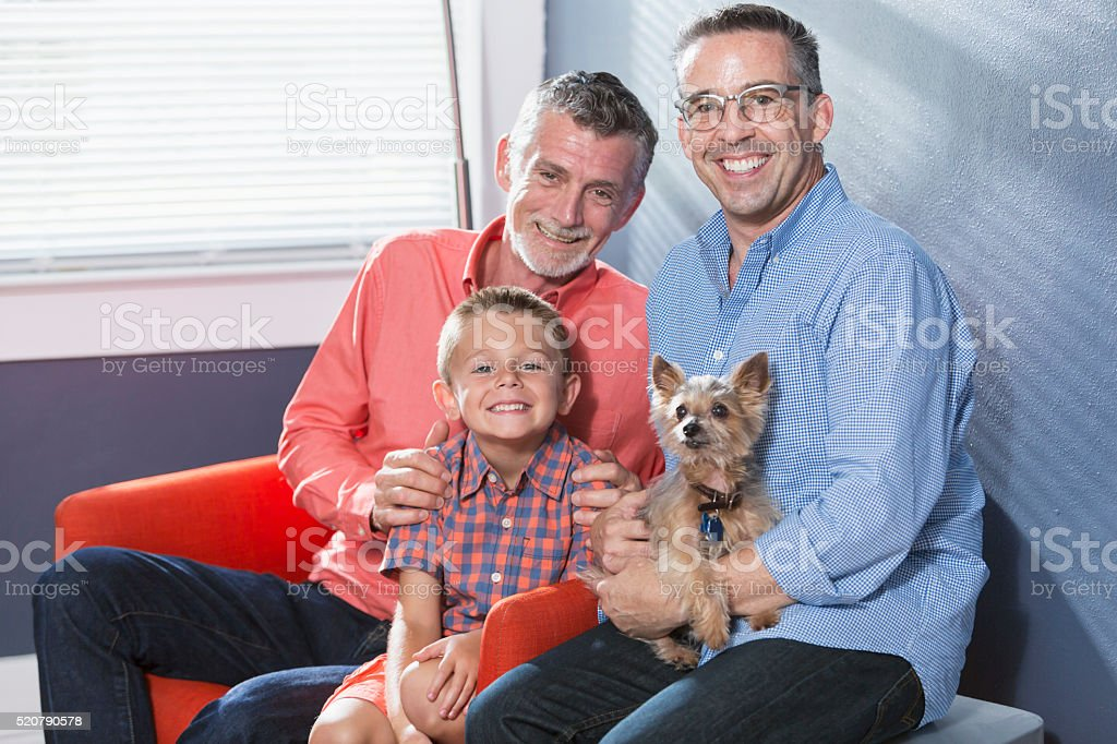 Two men, boy and little dog sitting by window stock photo