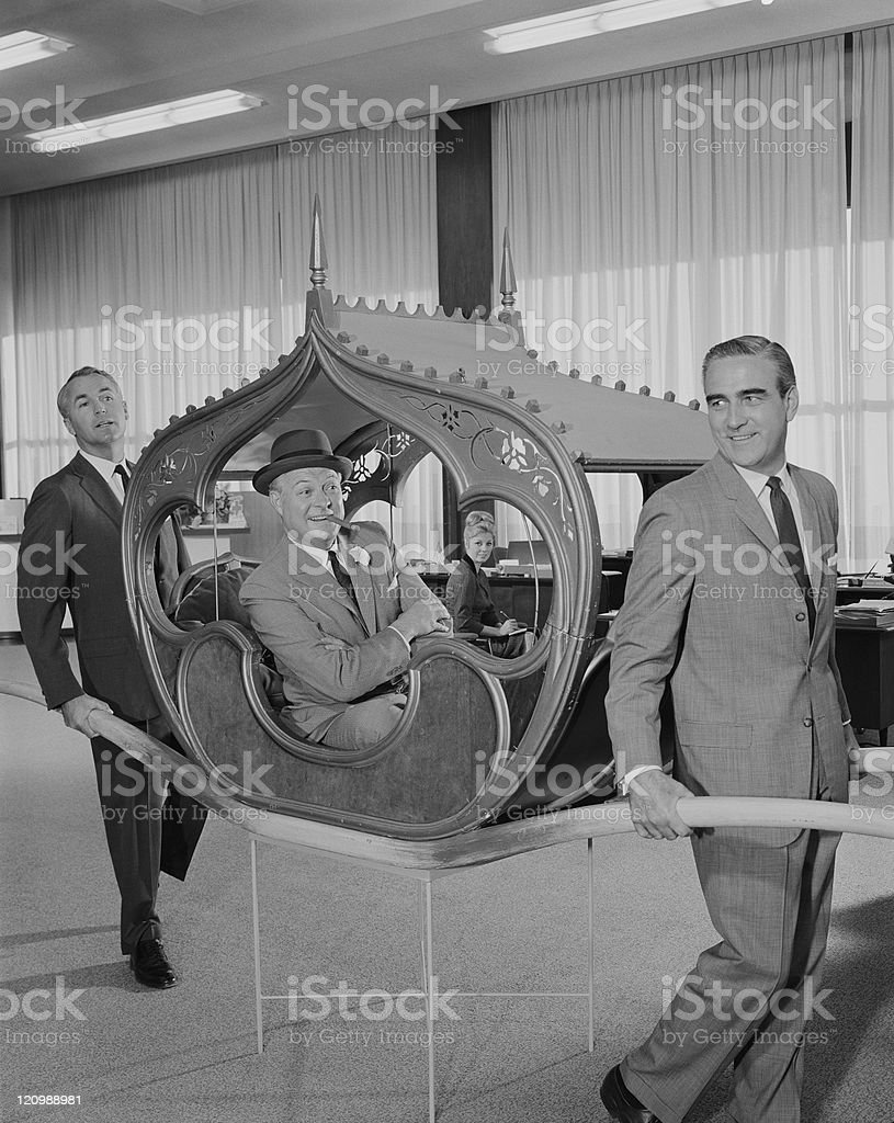 Two men carrying man on sedan chair stock photo