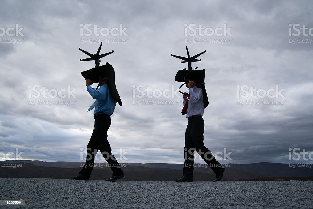 Two men carrying office chairs outdoors stock photo