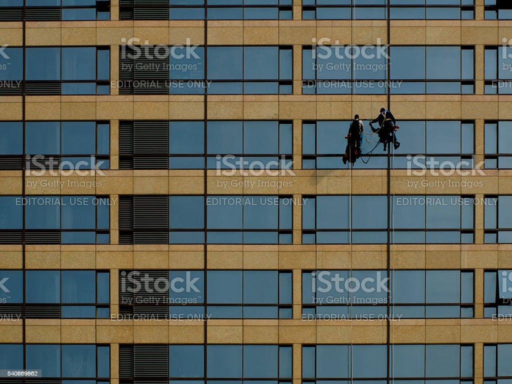 Two men clean the high-rise building. stock photo