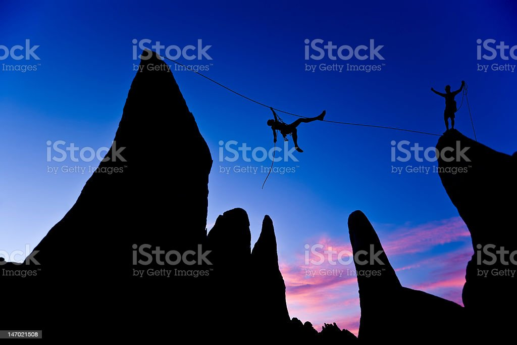 Two men climbing a rope between mountain peaks at dawn stock photo