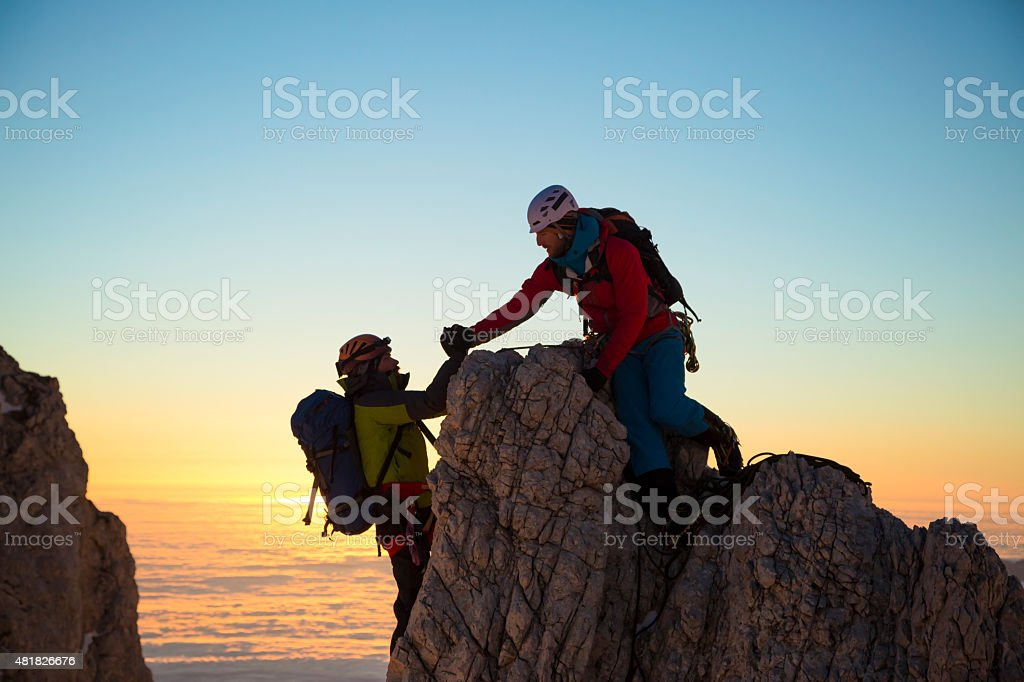 Two men climbing on rock stock photo