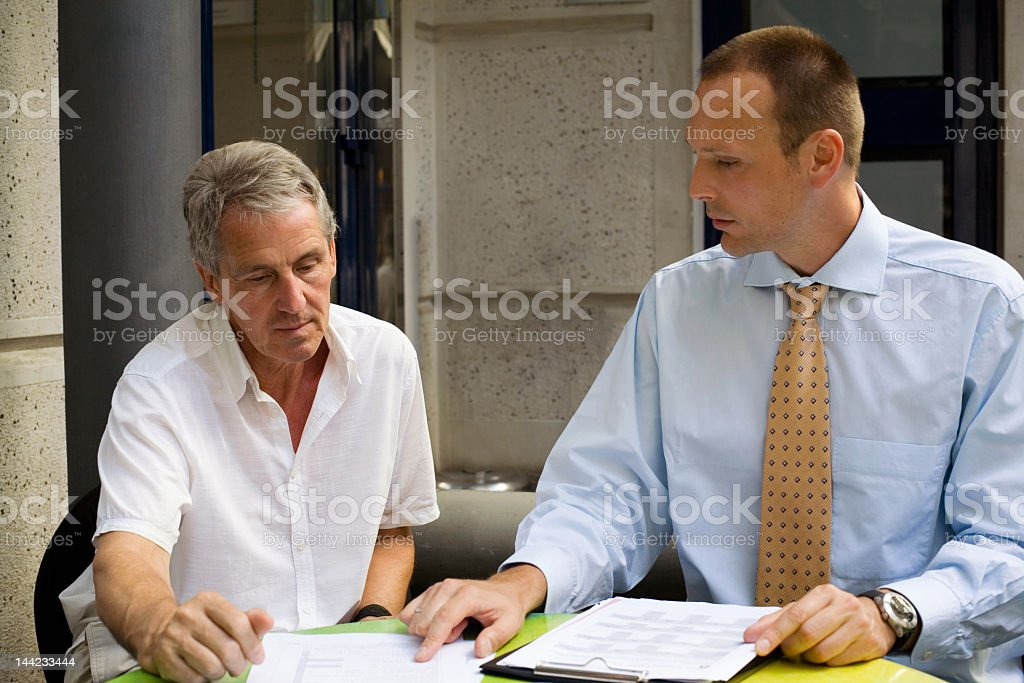 Two men compare notes at a meeting royalty-free stock photo