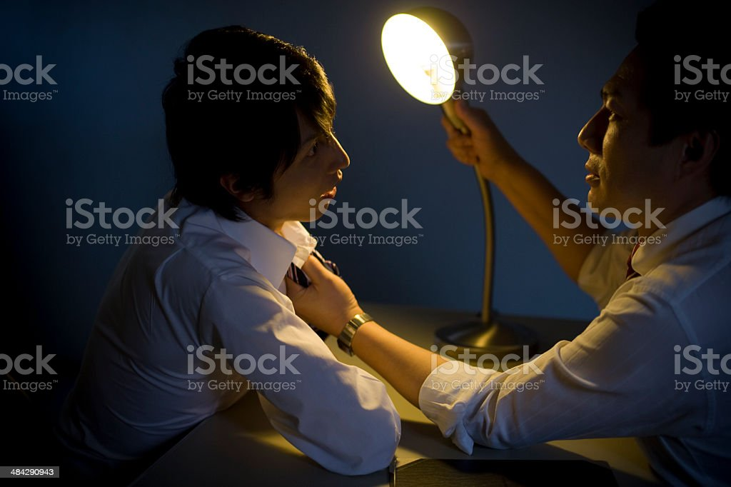 Two men confronting each other in interrogation room stock photo