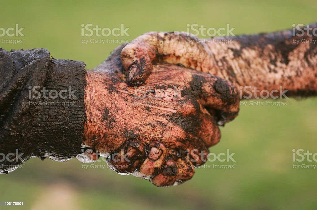 Two Men Covered in Mud Shaking Hands stock photo