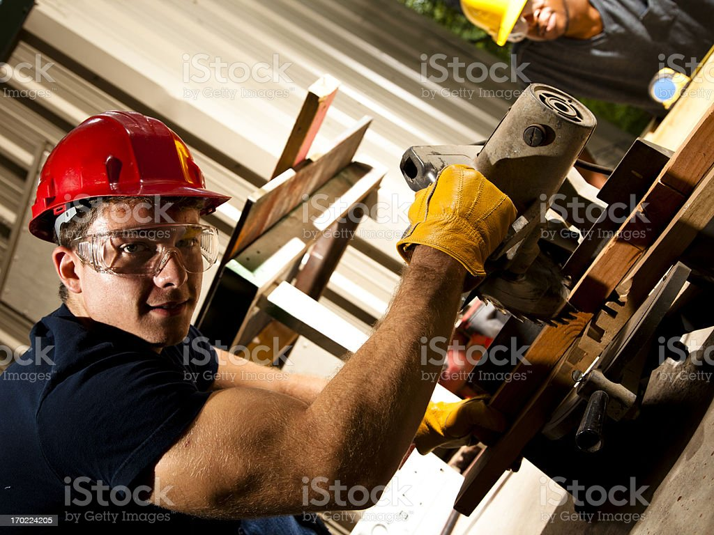 Two men cutting and measuring on construction job royalty-free stock photo