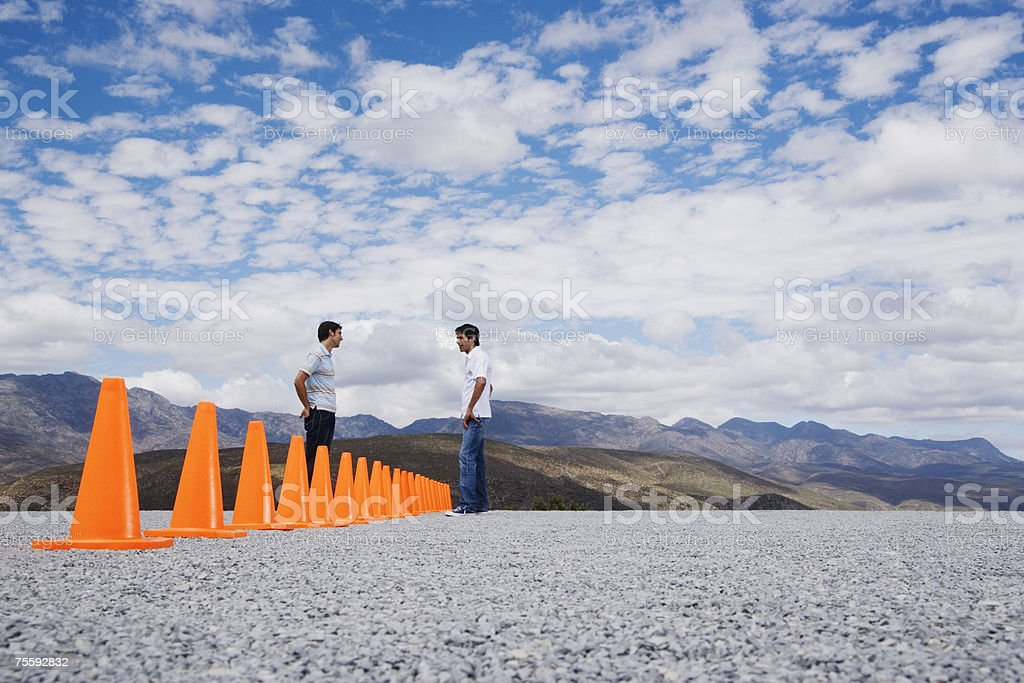 Two men divided by a row of safety cones stock photo