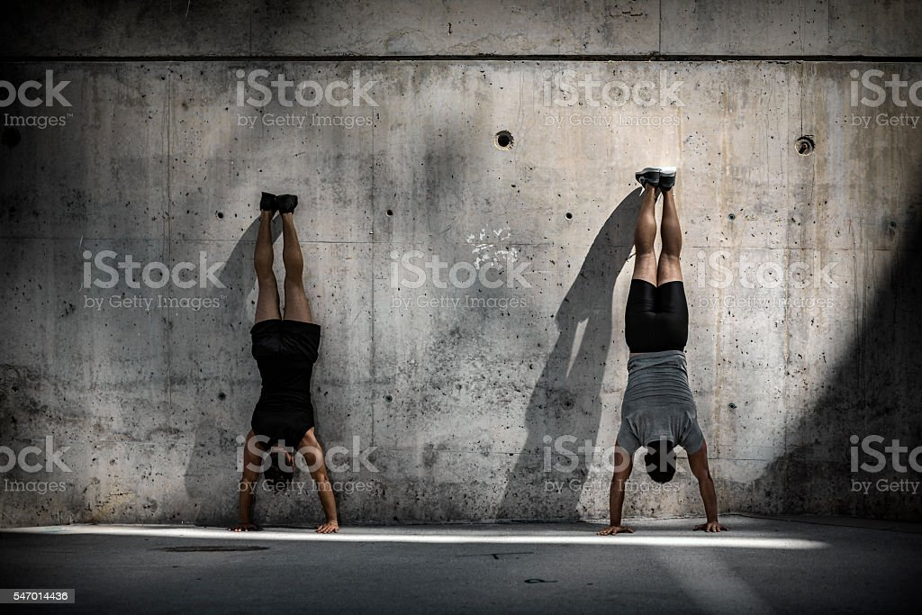 Two men doing headstands stock photo