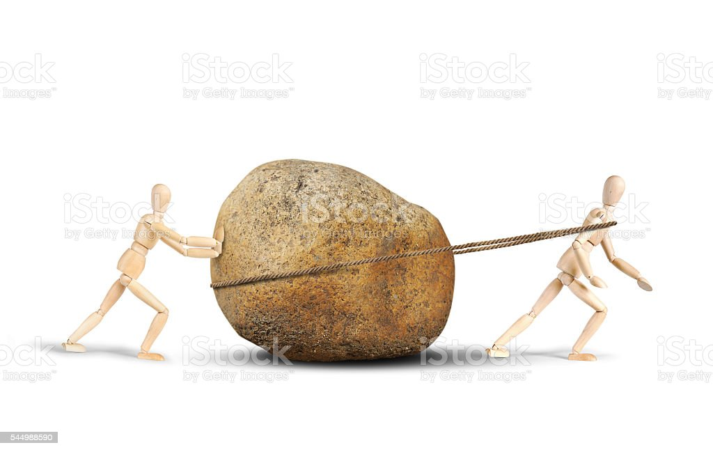 Two men drag a huge stone stock photo