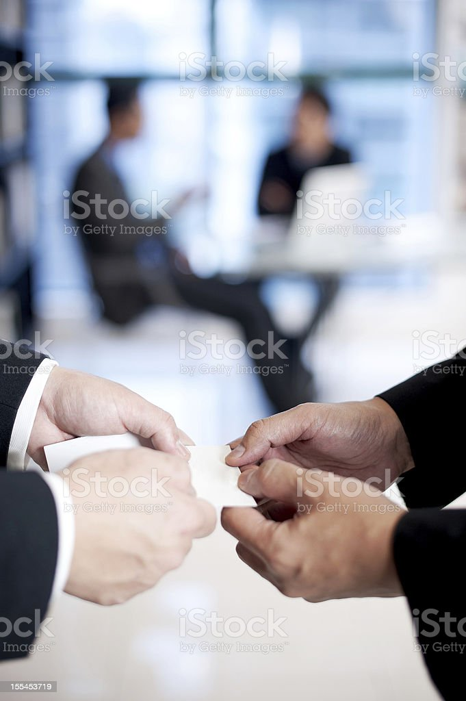 Two men exchanging business cards stock photo
