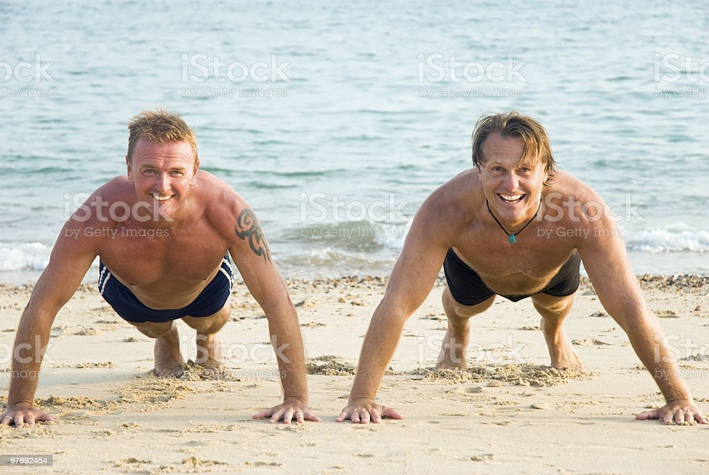 Two men exercising on beach. royalty-free stock photo