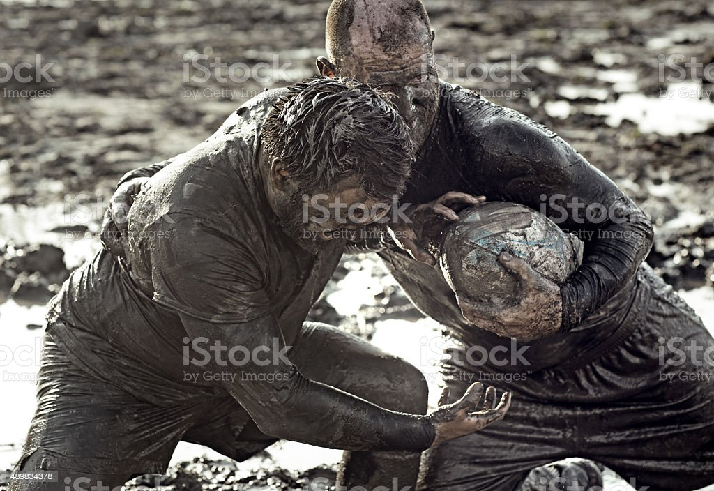 Two men fighting for rugby ball in mud stock photo