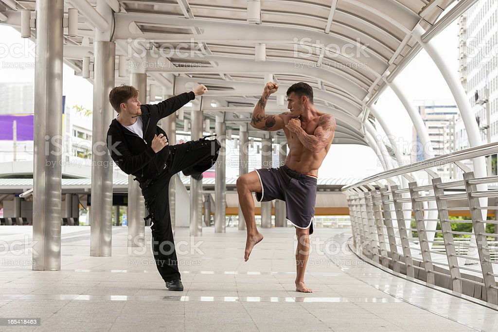 Two men fighting in urban environment stock photo