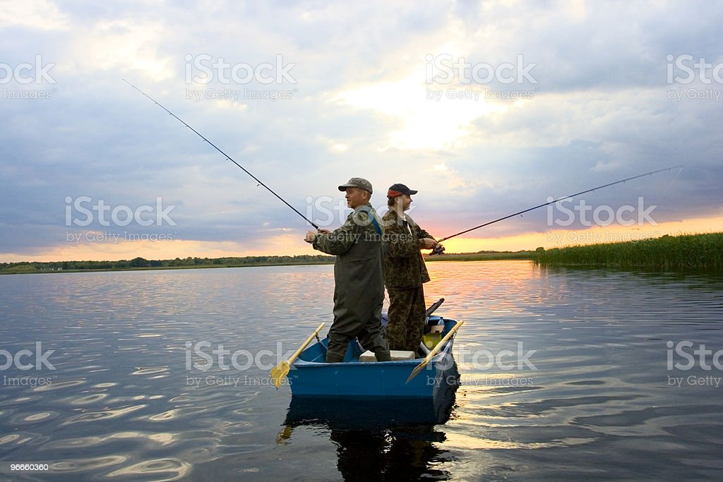 Two men fishing in a small boat pointing opposite ways stock photo